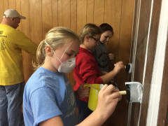 Cadet Regan Lavinder, C/Amn Sarah Benson, and C/Amn Marissa Haskell paint the seams in the paneling.